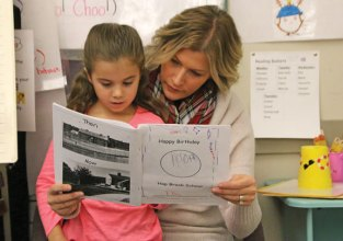 Hop Brook Elementary School first-grader Ella Brown reads to her mother, Krissy Brown, Dec. 9 as part of the school's centennial celebration in Naugatuck. In celebration of the school's 100th anniversary each of the grades worked on a different project. First-graders researched and wrote a page for a book comparing what school was like 100 years ago to today. –ELIO GUGLIOTTI