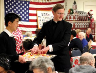 Brother Daniel Carter, right, serves fruit cocktail to seniors with the help of Brother Anselm Kim Dec. 8 during the Naugatuck Senior Center's annual Christmas Dinner. Carter and Kim were part of a group from the Legionaries of Christ in Cheshire that helped out at the dinner and sang for the seniors. –ELIO GUGLIOTTI