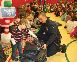 Maple Hill Elementary School first-grader Jacob Neal helps Naugatuck firefighter Nick Traycheff fill a bag with toys on Dec. 16 during the school's holiday celebration. The students held a toy drive in collaboration with the Naugatuck Fire Department. –LUKE MARSHALL