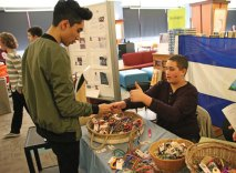 Freshman Donte Kontts, right, shows off a bracelet to sophomore Mohammad Khan March 8 during a Cultural Expo at the school. The expo, which coincided with National Foreign Language Week, featured displays and activities related to the countries where they speak languages taught at NHS, including Spain, Mexico, France, and Italy. The bracelets, called 'pulseras,' are made in Nicaragua by local artists. The money raised from the sale of the bracelets goes toward the artists and raising awareness about poverty in the country. –LUKE MARSHALL