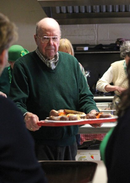 Volunteer Bud Cushman carries a platter with lunches on them ready to be served during a St. Patrick's Day lunch at the Naugatuck Senior Center on March 17. –ELIO GUGLIOTTI