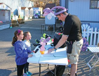 Sisters Katie, left, and Carly Luchina, both 6 of Naugatuck, watch as Kurt Beckley from Balloon Benders makes balloon animals during the Naugatuck Parks and Recreation Department's annual Easter Village April 14. –LUKE MARSHALL