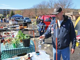 Dwayne Nelson, of Naugatuck, straightens out an air plant display during the Peddler's Market flea market April 23 on Parcel B in downtown Naugatuck. Nelson was one of a handful of vendors at the market, which reopened in the borough after shutting down in 2005. The market runs every Sunday through November. –LUKE MARSHALL