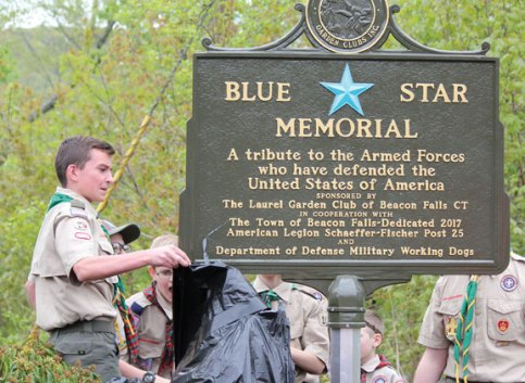 Members of Boy Scout Troop 104 in Beacon Falls unveil a Blue Star Memorial Marker on the town's streetscape during a dedication ceremony May 7 at the corner of Depot Street and South Main Street. The Blue Star program, which is overseen by the National Garden Clubs, Inc., honors those who served in every branch of the armed forces. The Laurel Garden Club of Beacon Falls sponsored the town's marker, which also recognizes military dogs. –ELIO GUGLIOTTI