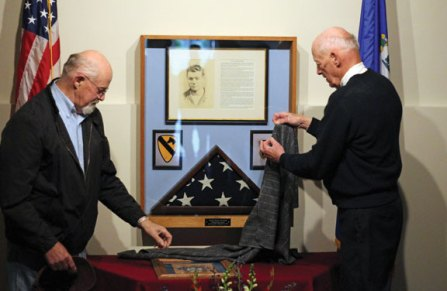 Peter Merriman, left, and his brother, Doug Merriman, unveil a memorial dedicated to their brother, Roy Thomas Merriman, on Monday, Memorial Day, at the Prospect Community Center. Roy Thomas Merriman, who was known as 'Tommy,' was killed in action on Sept. 7. 1950 during the Korean War. The American Legion Post 194 in Prospect is named after Tommy Merriman. The memorial includes a sketch of Tommy Merriman, a brief biography, and the flag that was on his grave at Arlington National Cemetery in Virginia. –ELIO GUGLIOTTI