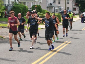 Naugatuck police Officer Jacob Pinho, right, hands the torch to Patrolman James Tortora in front of the Naugatuck Police Department on Spring Street June 8 during the Law Enforcement Torch Run for Special Olympics Connecticut. Naugatuck police officers carried the torch from the Cross Street Plaza to the Waterbury line on Spring Street where they handed the torch to members of the Waterbury Police Department. –LUKE MARSHALL