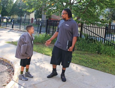 Hop Brook Elementary School third-grader Andre Jackson, Jr., 8, talks with his father, Andre Jackson, Sr., outside the elementary school in Naugatuck before the start of the first day of school on Aug. 28. –LUKE MARSHALL