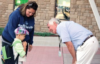 Region 16 Board of Education Vice Chair Robert Hiscox, right, greets Prospect Elementary School kindergartner Nikolas Mitchell, 4, and his mother, Nicole Mitchell, on the first day of school Aug. 28 at the school in Prospect. –ELIO GUGLIOTTI
