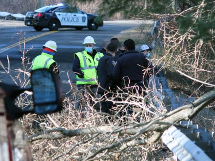 Police officers, firefighters and Metro-North Authority workers gather where a Honda Accord crashed down an embankment off Cold Spring Road in Beacon Falls on Monday. -ELIO GUGLIOTTI