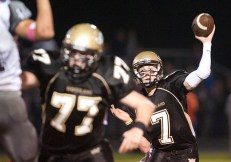 Woodland's Tanner Kingsley (7) throws a pass while Alik Bures (77) blocks during a game against Naugatuck in 2013 at Woodland Regional High School in Beacon Falls. –REPUBLICAN-AMERICAN ARCHIVE
