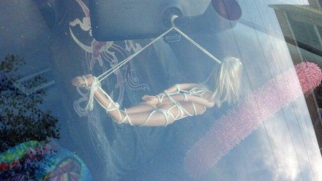 Bondage Barbie hanging from a car.jpg
