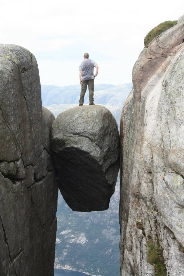 stuffofawesome-oh-just-standing-on-a-boulder-stuck-between-two-cliffs-3000-feet-above-the-fjord-below-1313622006-701