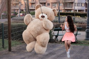 girl with big teddy bear on swing 4k
