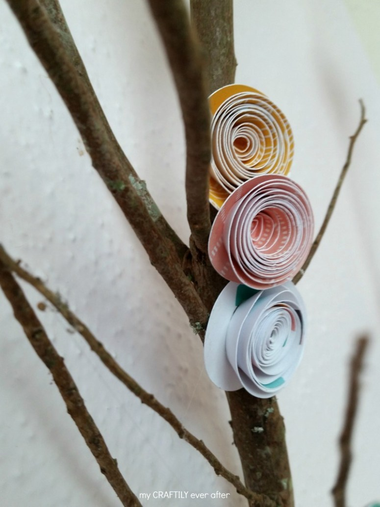 rolled paper flowers on a branch