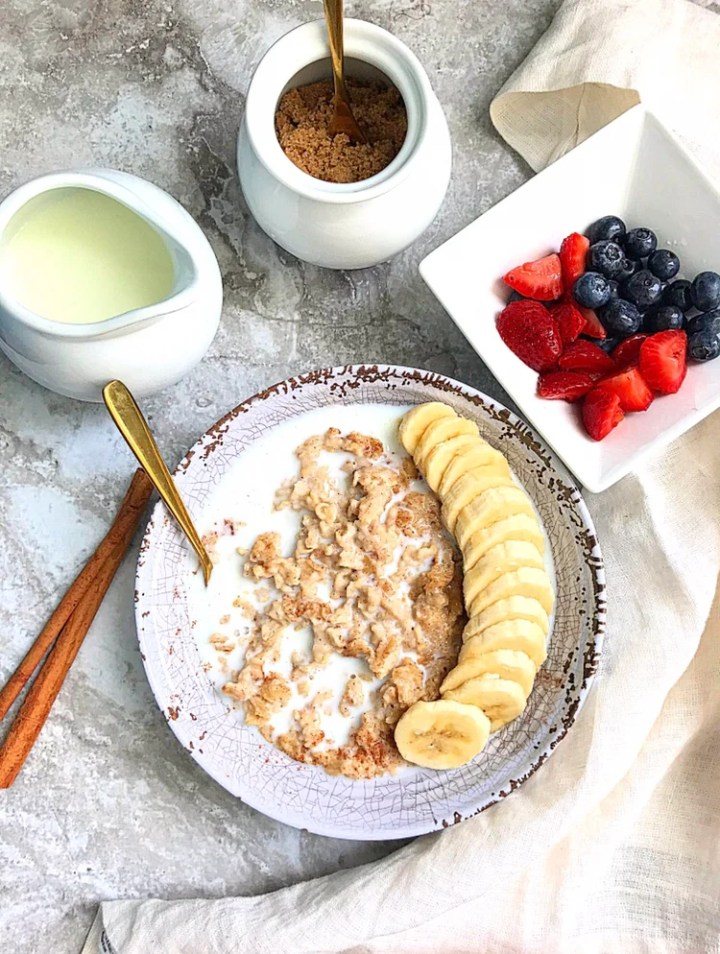 cinnamon and oatmeal porridge, a mini jug of milk, a bowl of brown sugar and a bowl of strawberries and blueberries