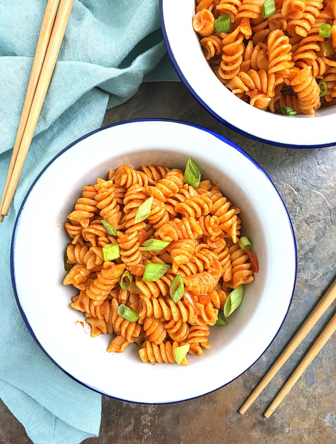 Top view coconut Rotini pasta in a white bowls on a brown background with a blue hand towel plus chopsticks on the sides
