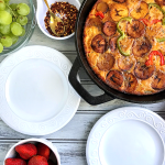 Plantain frittata in a skillet with two empty plates and fruits around