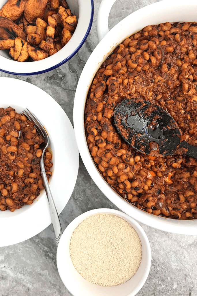 Ghanaian stewed Black eyed peas served with plantains and some cassava flakes in a small bowl