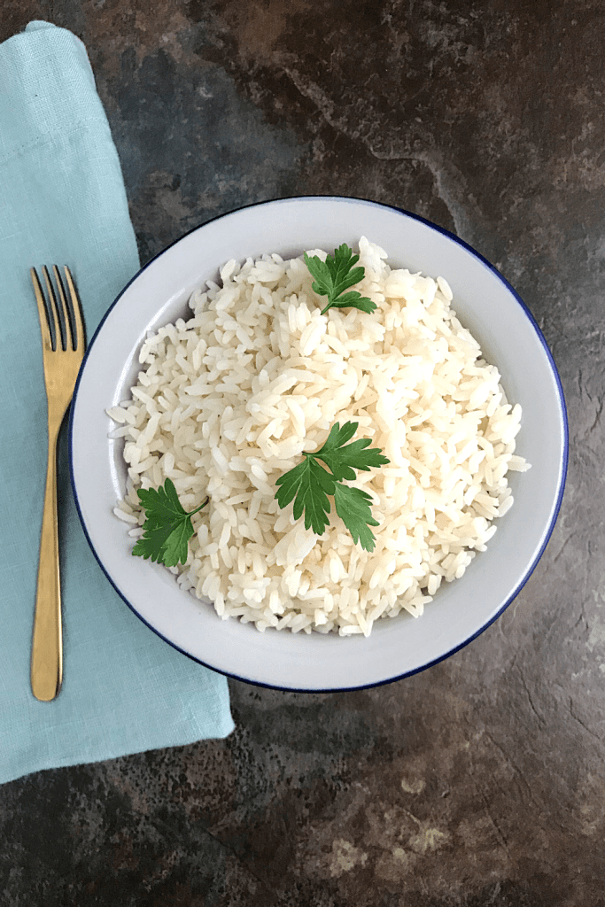 how to cook rice. White Rice in a plate garnished with parsley leaves