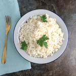 How to cook white rice; a plate of cooked white rice garnished with parsley