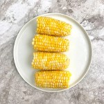 cooked corn on the cob in a round white plate