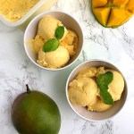 top view of mango ice cream in two green ice cream bowls surrounded by a whole mango and a cut up mango