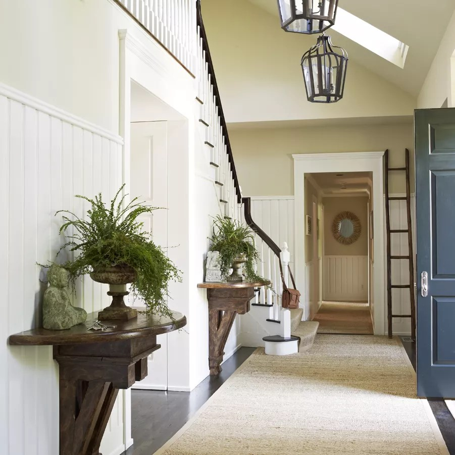 Large entryway with woven rug and pendant lights.