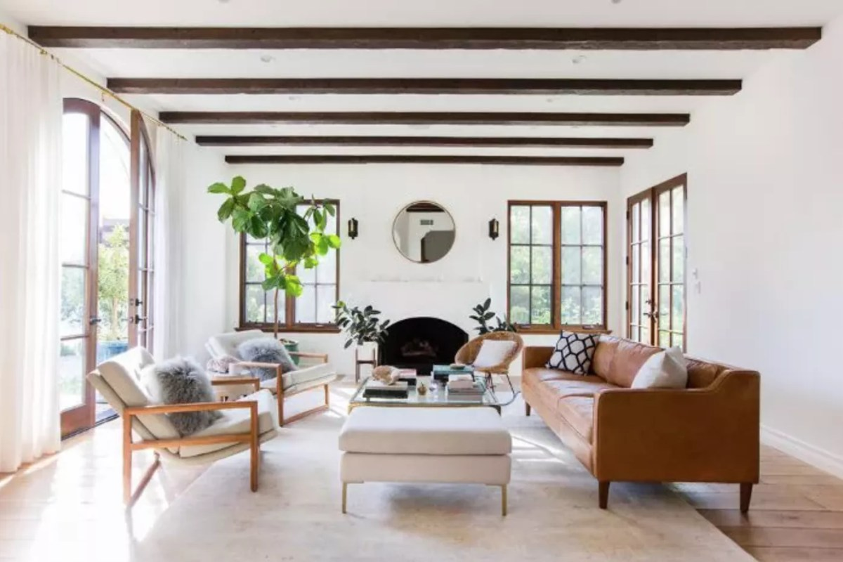 Living room features fiddle leaf fig tree and exposed-beam ceiling