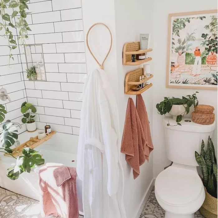 white bathroom with plants, wicker floating shelves holding items, toilet with painting hanging above it