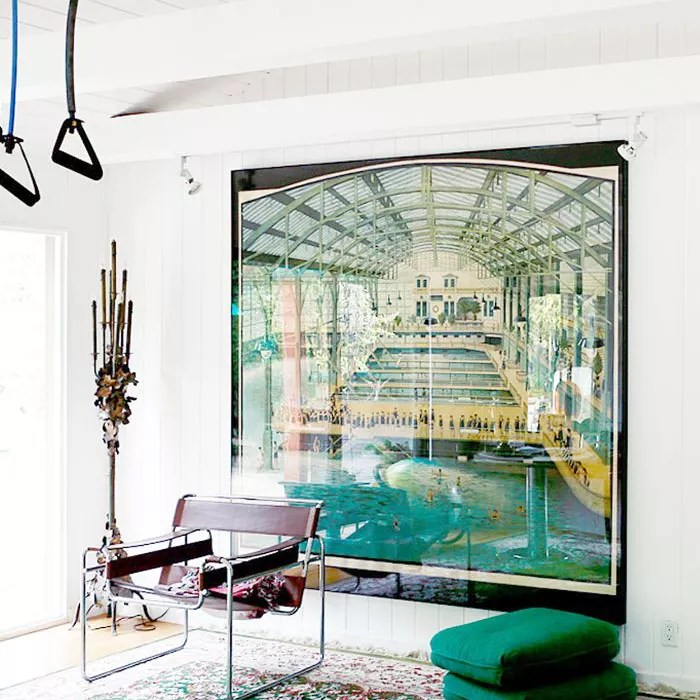 A large-scale photo of Sutro Baths in a spare room with green patterned rug