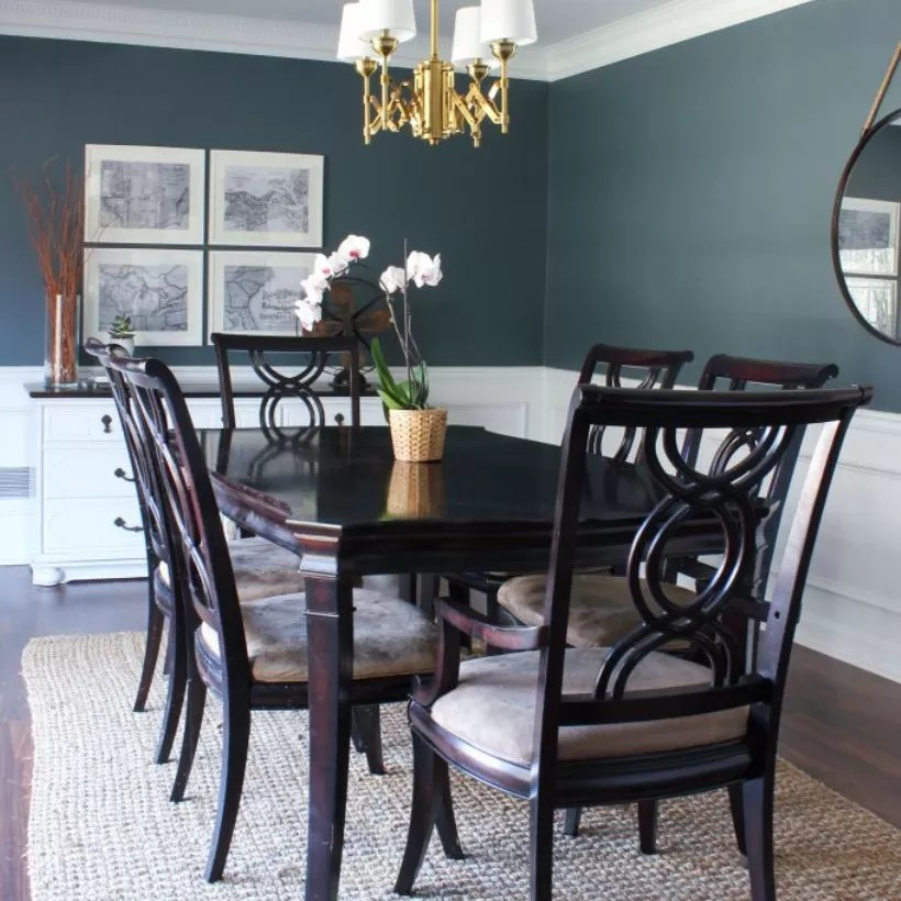 Updated traditional dining room with slate blue walls, white paneling, and dark wood furniture.
