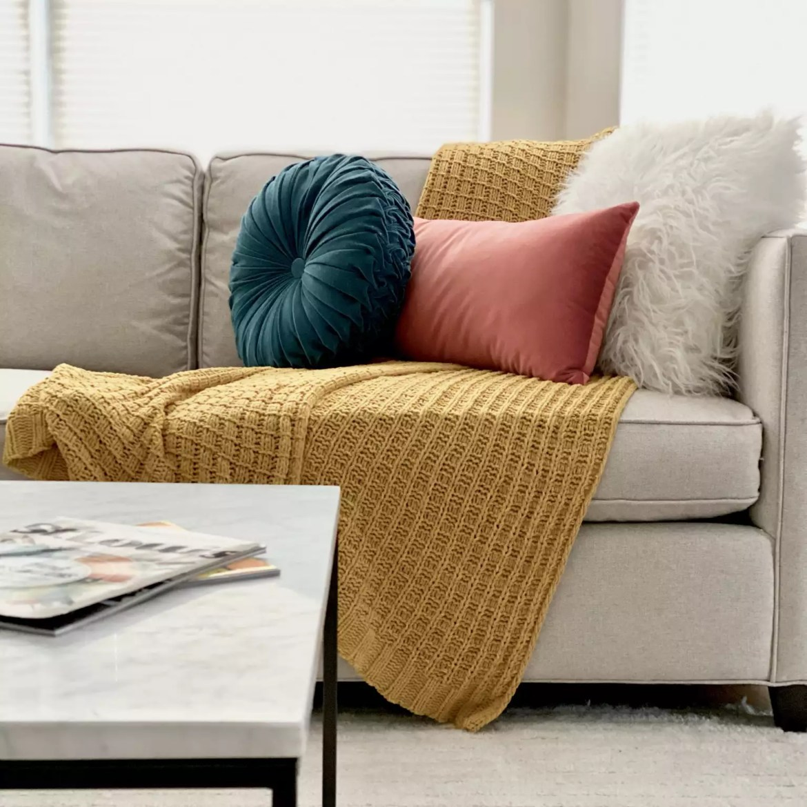 Sofa with mustard throw blanket and velvet pillows.