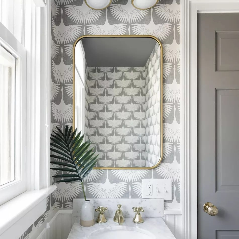 Gray bathroom with patterned gray and white wallpaper.