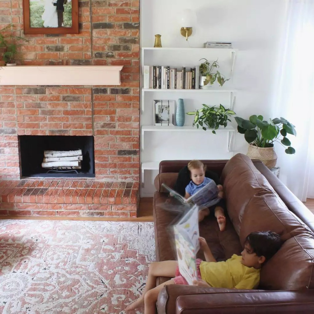 Dwell Aware cozy living room with brick fireplace.