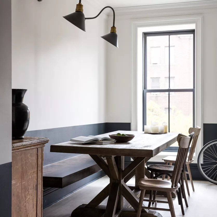 A kitchen table in a room that's been painted black at the bottom and white at the top
