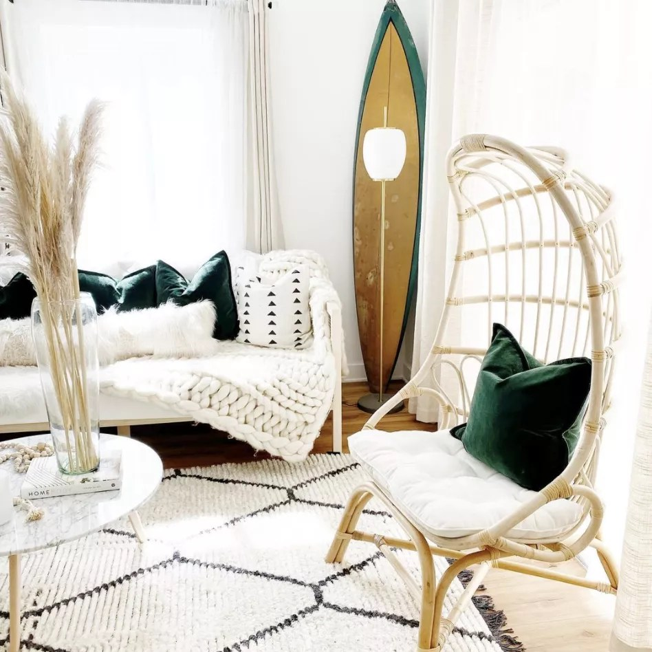 Beachy coastal living room with surfboard and rattan egg chair.