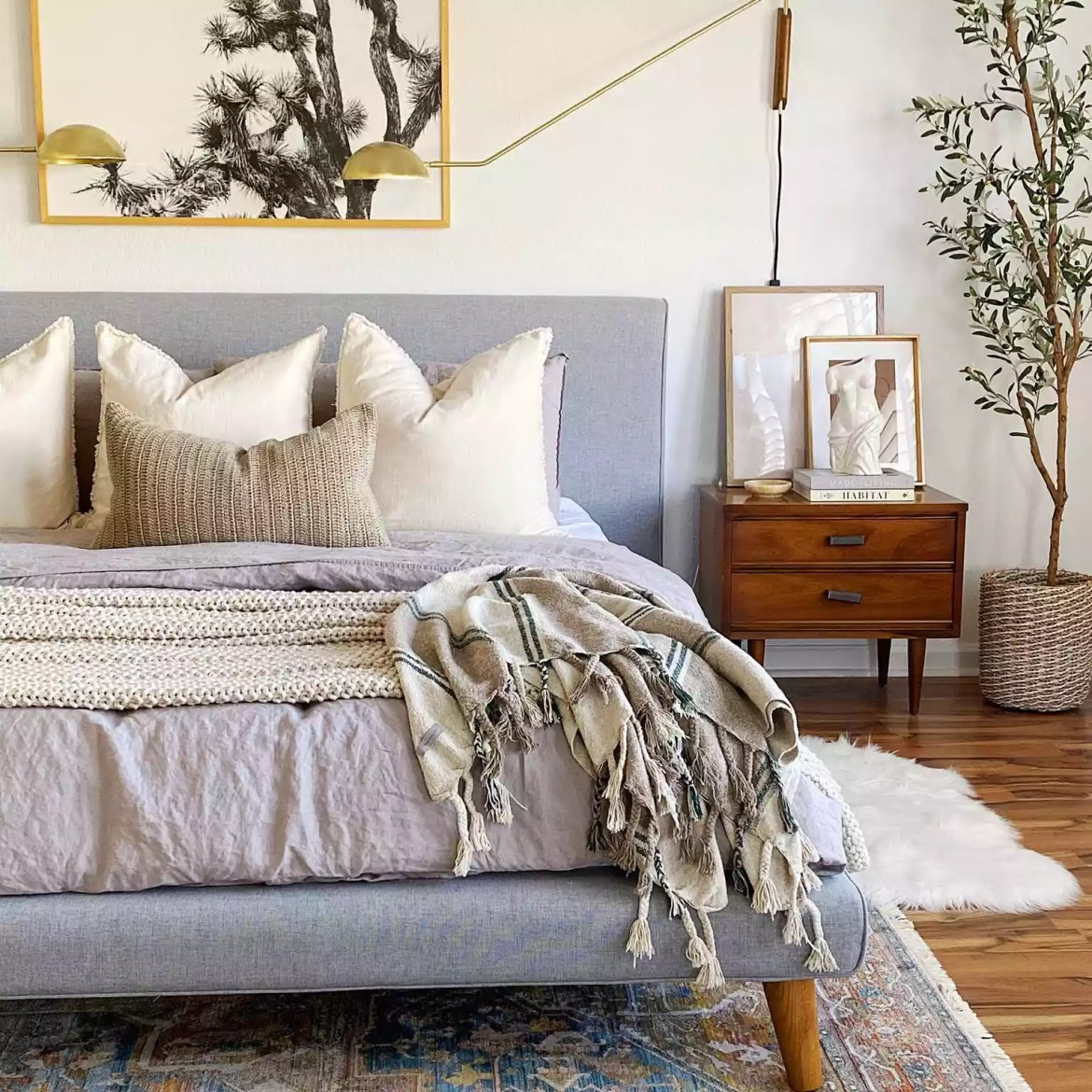 Neutral bedroom with vintage rug and gold lighting.