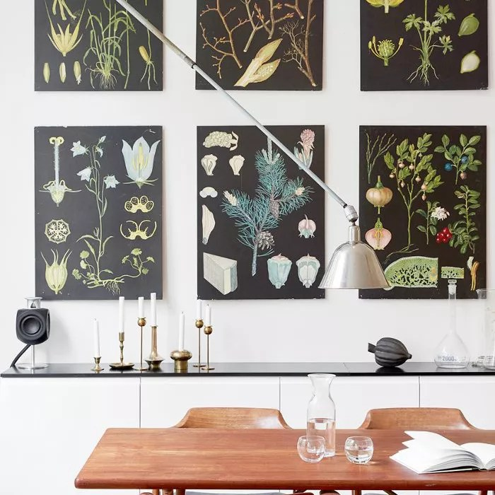 Gallery of wall prints complements a dining room