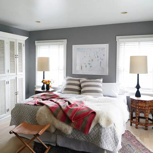 Soft bedroom with striped pillows and blanket.