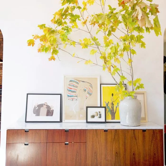 A collection of framed art and plant in a vase in the foyer
