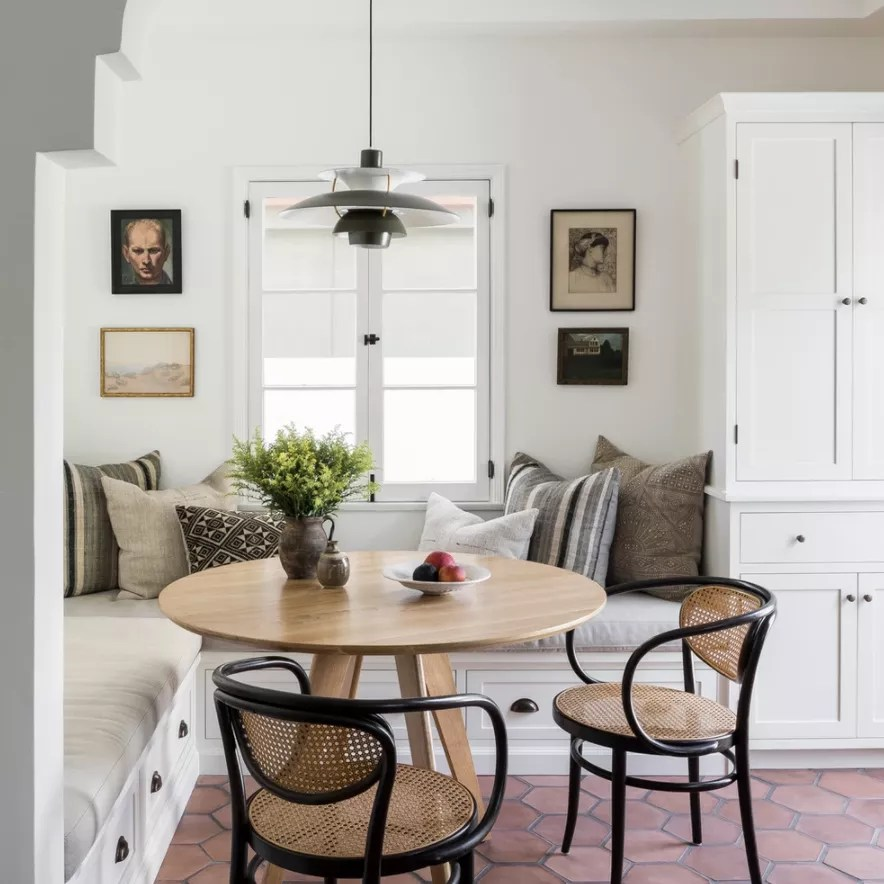 A kitchen corner with a built-in banquette topped with cushions