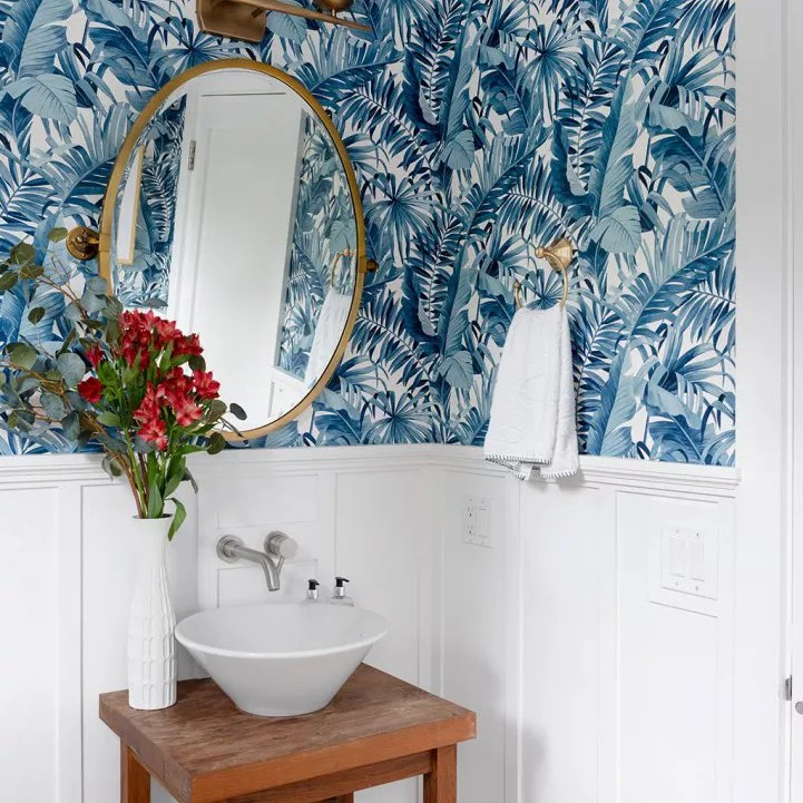 Fun half bathroom with blue printed palm wallpaper.