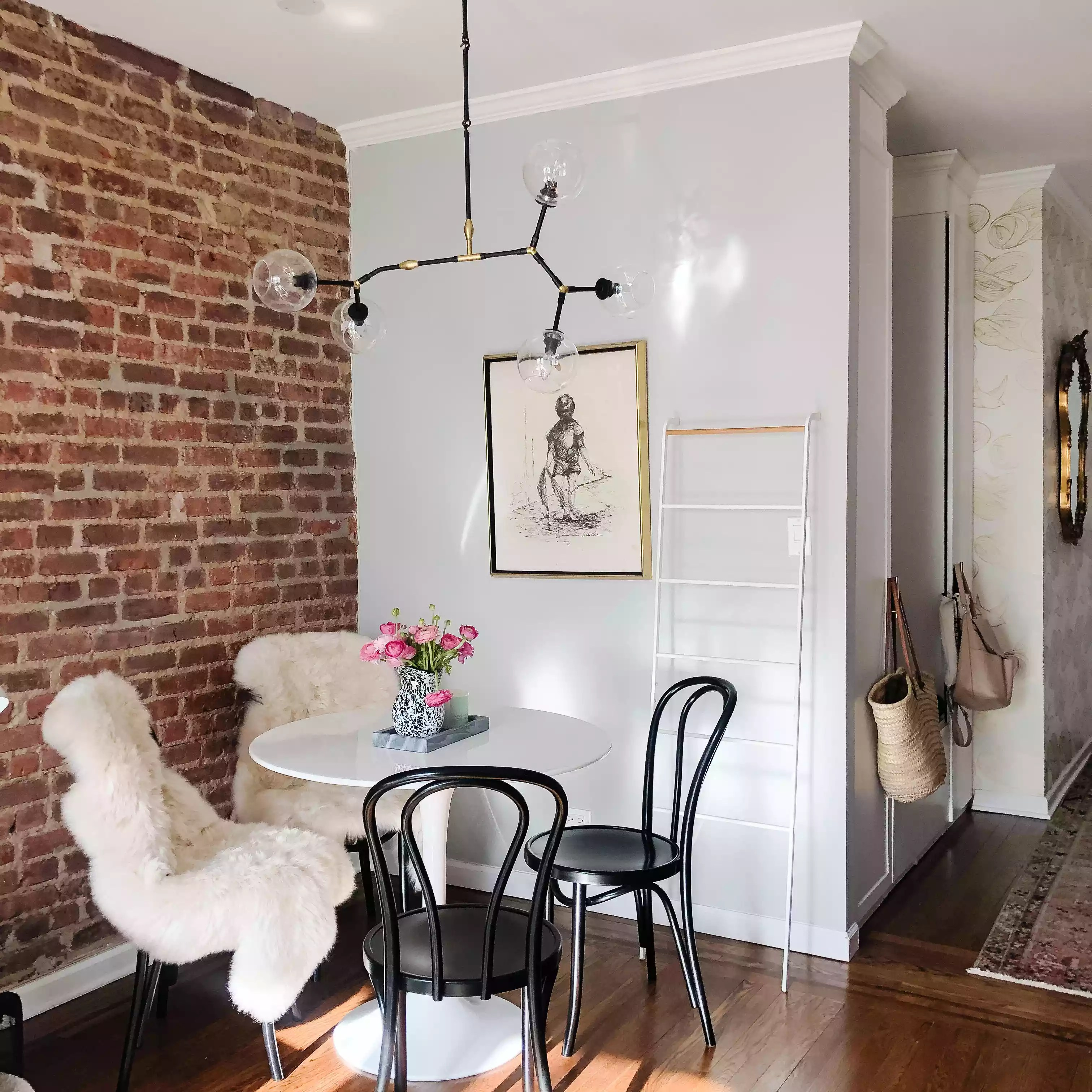 Small dining nook against brick wall.