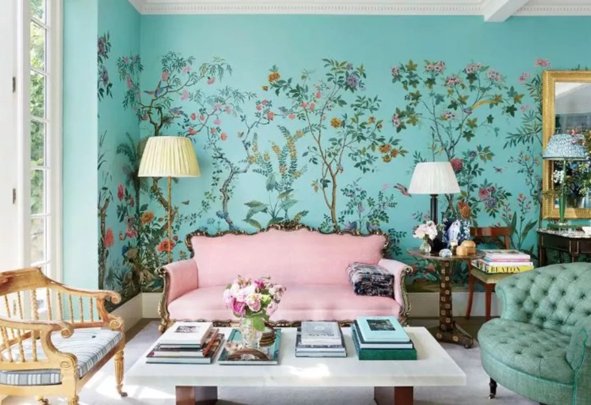 Aqua and floral wall paper in living room, pink loveseat flanked by lamps and a side table