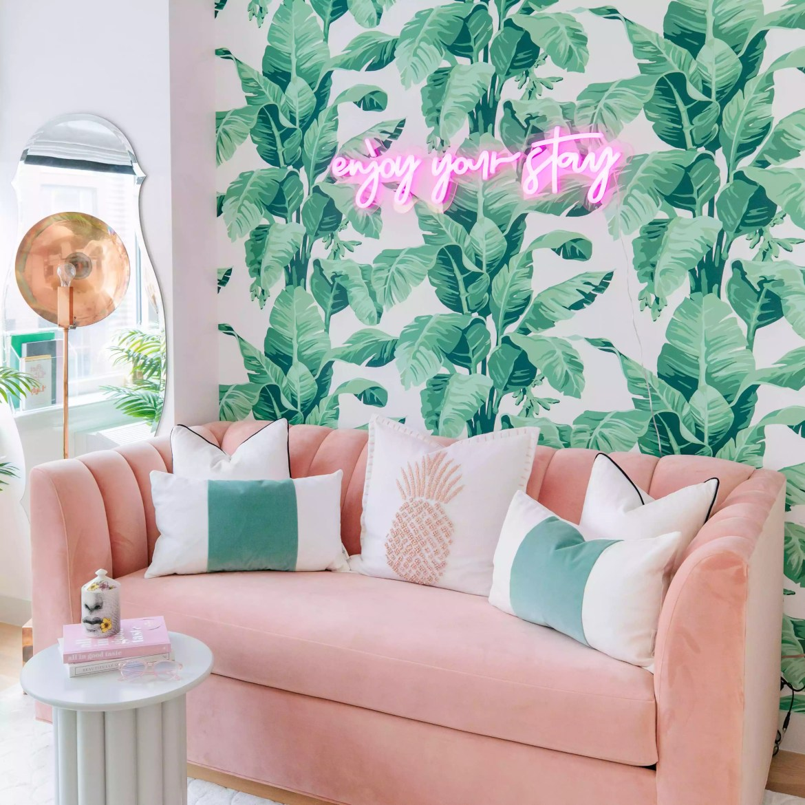 Guest room with banana leaf wallpaper and neon sign.