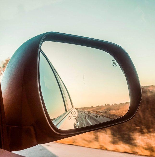 side mirror of car on road trip