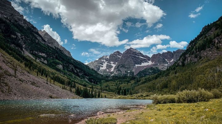 mountain in aspen with snow and trees and grass and lake and clouds and sky