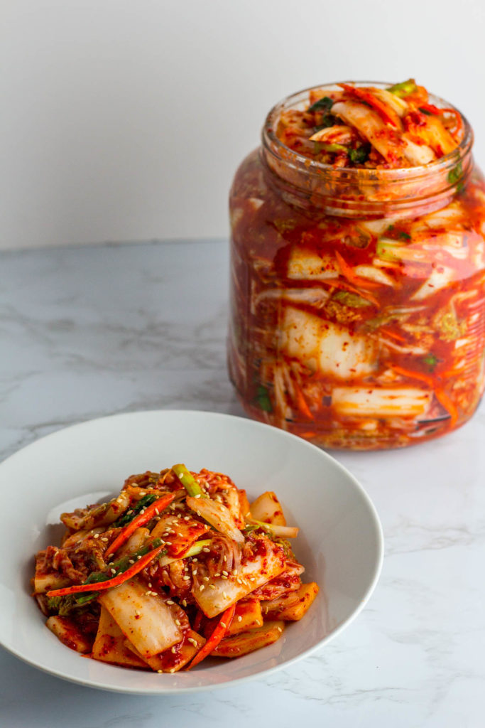 Vegan Kimchi in a big jar and plateful of freshly made kimchi in front