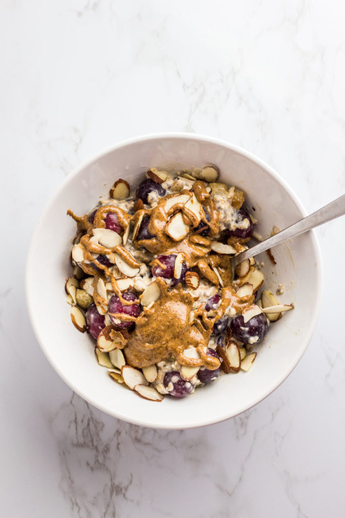 overnight oats in a white bowl with red grapes, almond slices, and almond butter drizzled on top