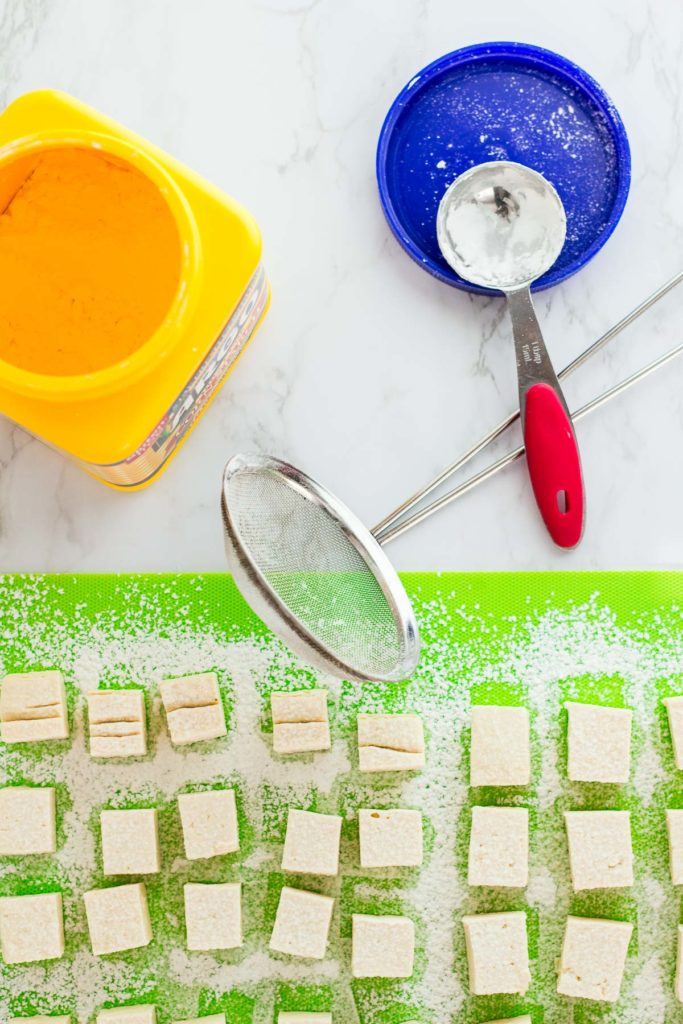 Tofu cubes dusted with corn starch, corn starch, and strainer-sifter in the background
